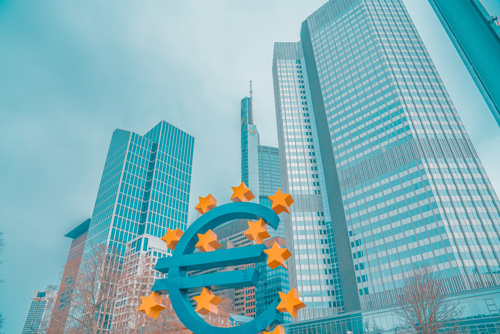 Euro sign monument with city in background